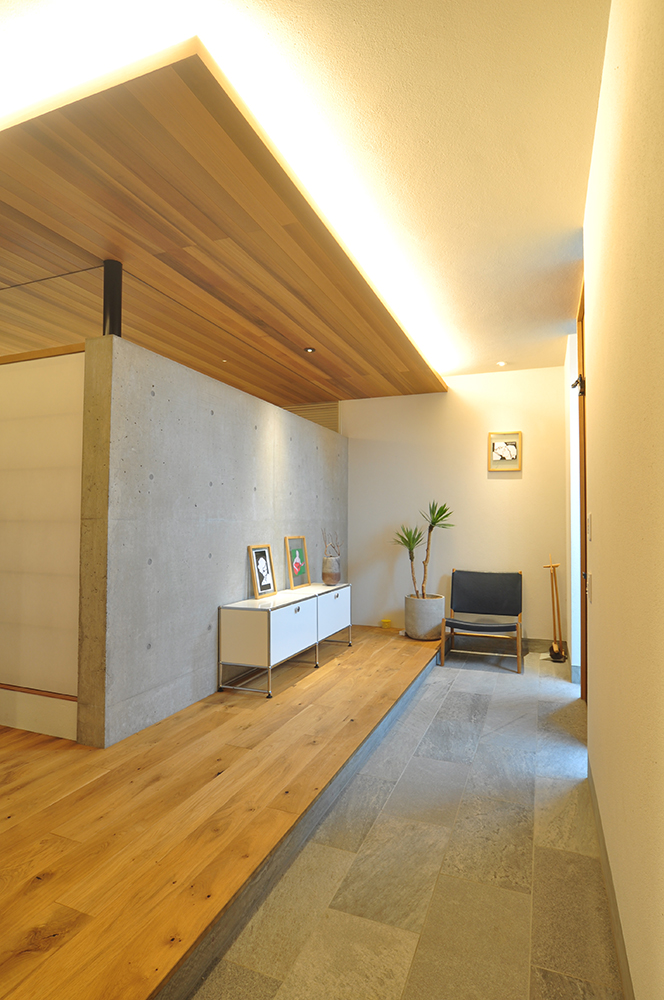 コンクリート打ちっぱなしのアクセントウォールと間接照明が印象的な玄関ホール