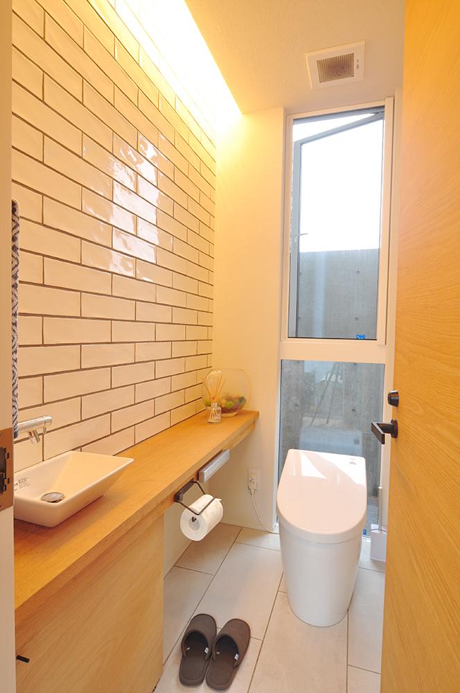 壁面タイルを魅せる間接照明があるトイレ