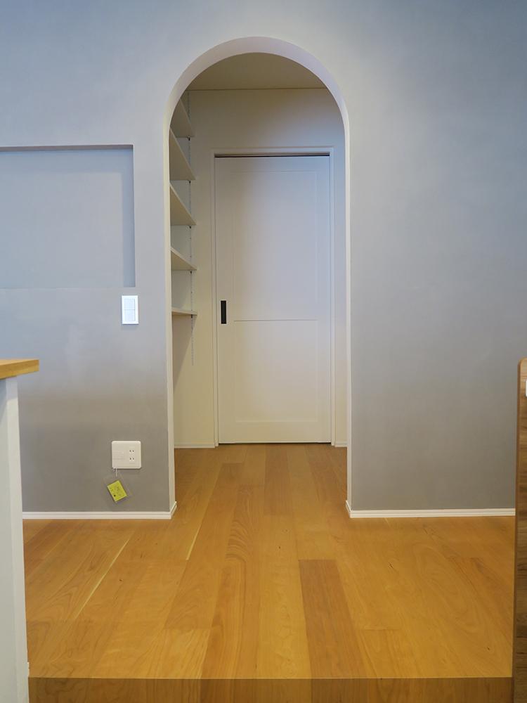 パントリーへ続く丸みのある開口がある壁は可愛らしくなりすぎないよう、グレーで落ち着いた印象に